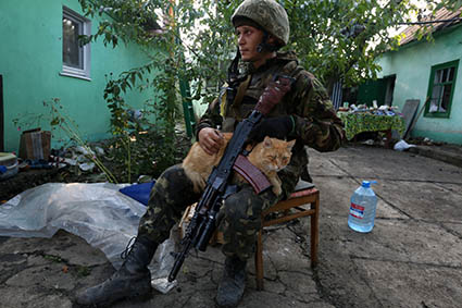 A Ukraine soldier is petting a local cat in the yard of a deserted house in the village of Peski on the outskirts of Donetsk on Saturday. Photo by Sergei L. Loiko Los Angeles Times